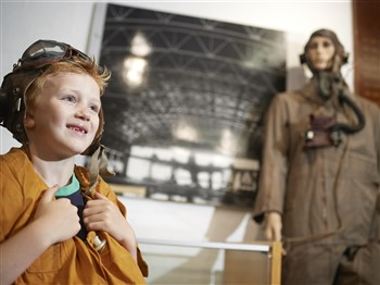 Young boy in a museum wearing a pilot's helmet