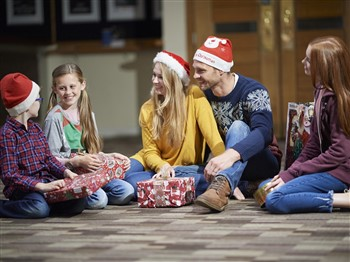 Family sitting giving Christmas presents