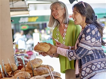 Ladies buying bread from a market