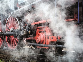 Close-up of steam train wheels with steam