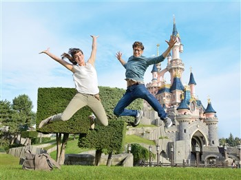 Couple jumping in front of the castle at Magic Kingdom