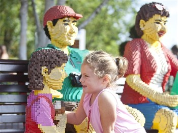 A small girl with a family made of Lego