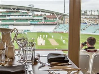 A table set for afternoon tea overlooking a cricket pitch